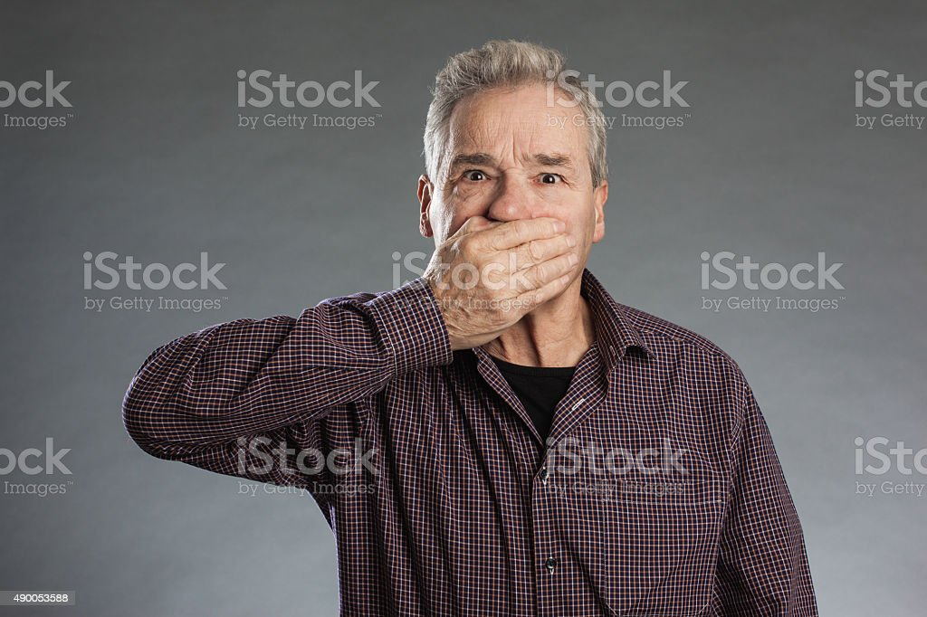 Male senior holding hands over mouth stock photo