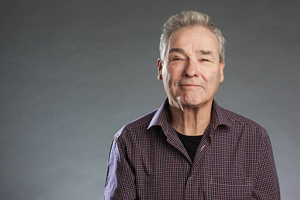 Male senior looking happily into camera. Horizontal portrait on Male senior looking happily into camera. Horizontal portrait on gray background with copy space one senior man only stock pictures, royalty-free photos & images