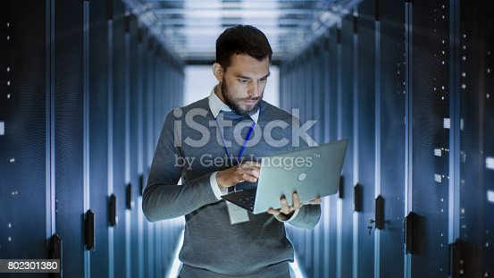 802303672istockphoto Male Server Engineer Works on a Laptop in Large Data Center. 802301380