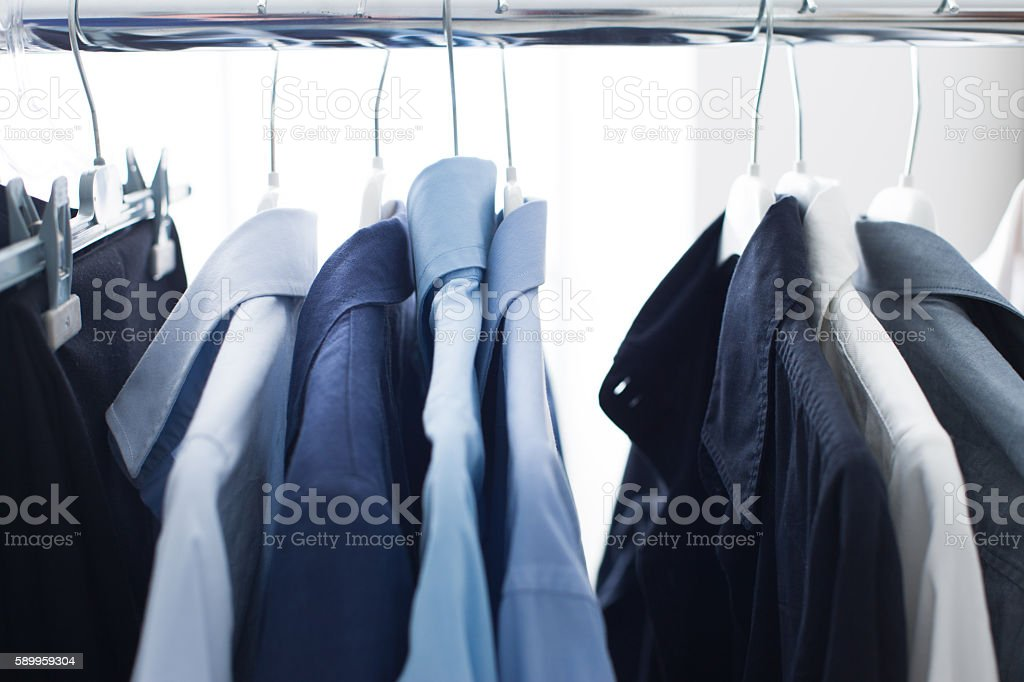 Male shirts hanging on a rack stock photo