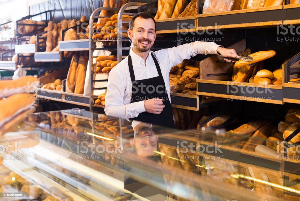 Male shop assistant demonstrating delicious loaves of bread in bakery stock photo