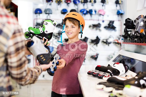 istock Male shop assistant helping boy to choose roller-skates in sports store 926172384