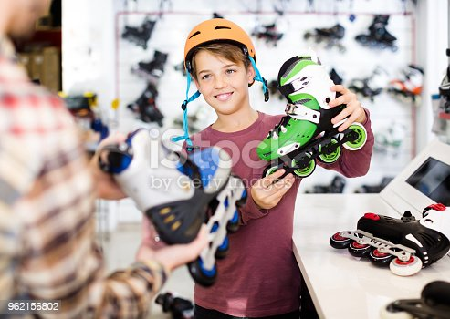 istock Male shop assistant helping boy to choose roller-skates in sports store 962156802