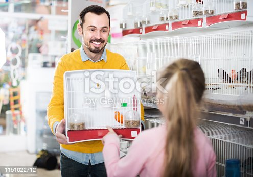Male shop assistant offering cage with canary bird to girl in pet shop