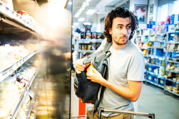 a male shoplifter stealing some expensive gourmet cheese in a supermarket - stealing crime stock photos and pictures