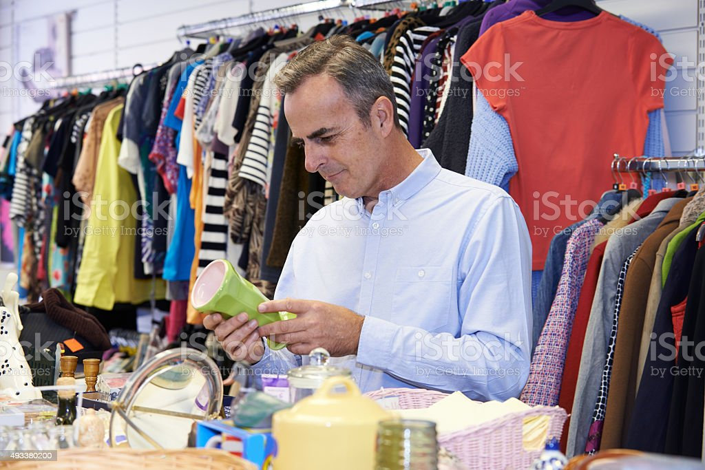 Male Shopper In Thrift Store Looking At Ornaments stock photo