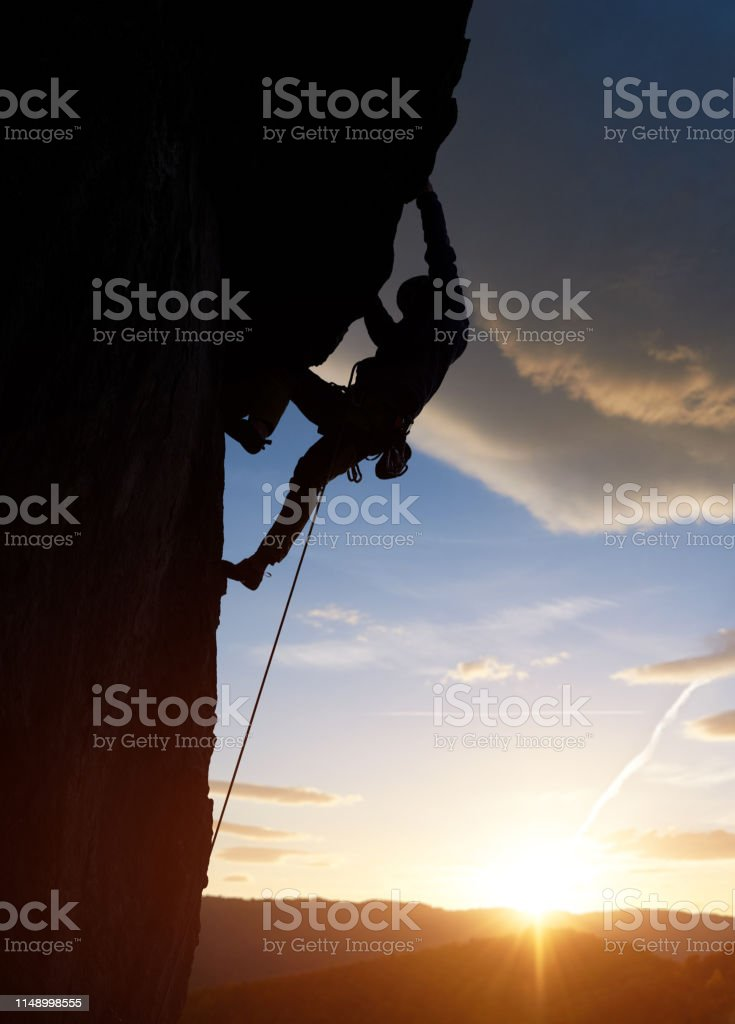 Male silhouette rock climbing, doing next step at sunrise in...