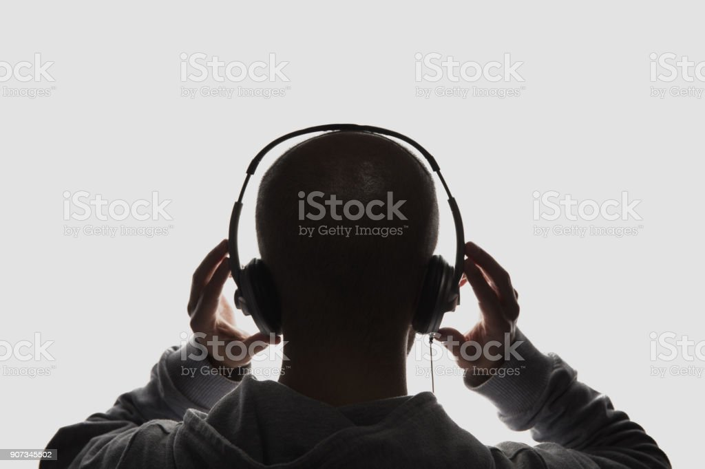 Male silhouette with hands holding headphones royalty-free stock photo