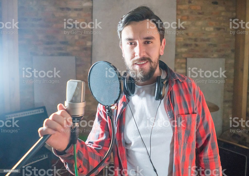 Male singer at a recording studio holding the microphone and looking...