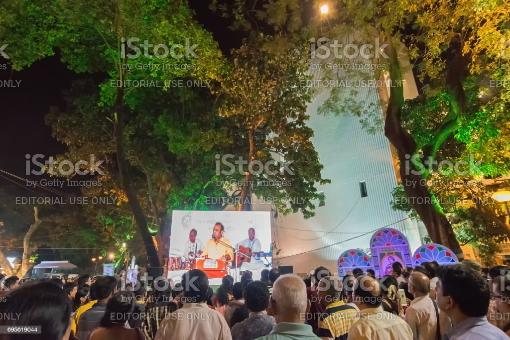 A male singer performing and seen in big screen amongst audience. stock photo