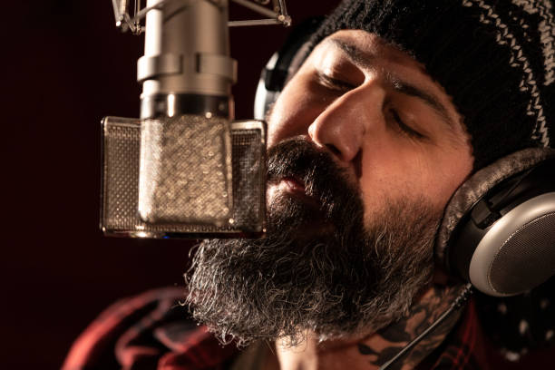 Male singer performing for recording in sound studio stock photo