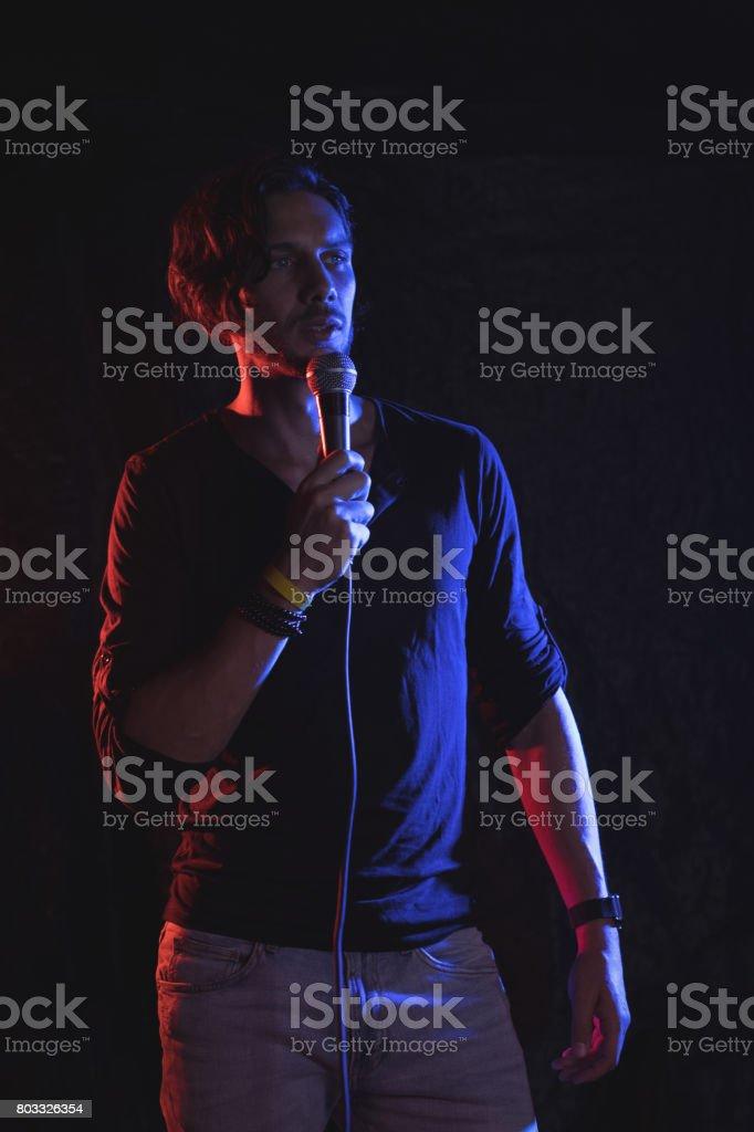 Male singer performing in illuminated nightclub stock photo