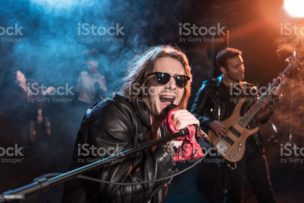 Male singer with microphone and rock and roll band performing hard rock music on stage - foto de acervo