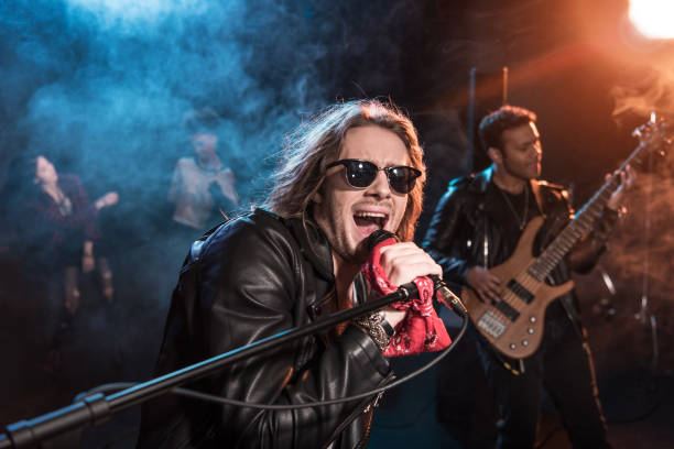 male singer with microphone and rock and roll band performing hard rock music on stage - rock music stock pictures, royalty-free photos & images