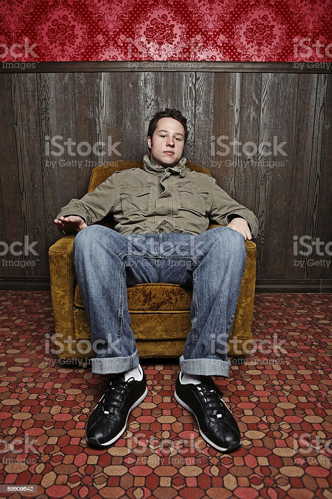 Male Sitting in Retro Room and Pattern Carpet royalty-free stock photo