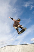 A male skateboarder catches some air out of the bowl.