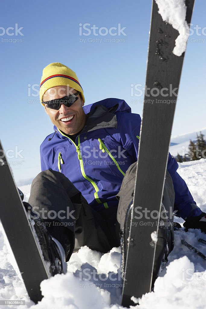 Male Skier Sitting In Snow With After Fall royalty-free stock photo