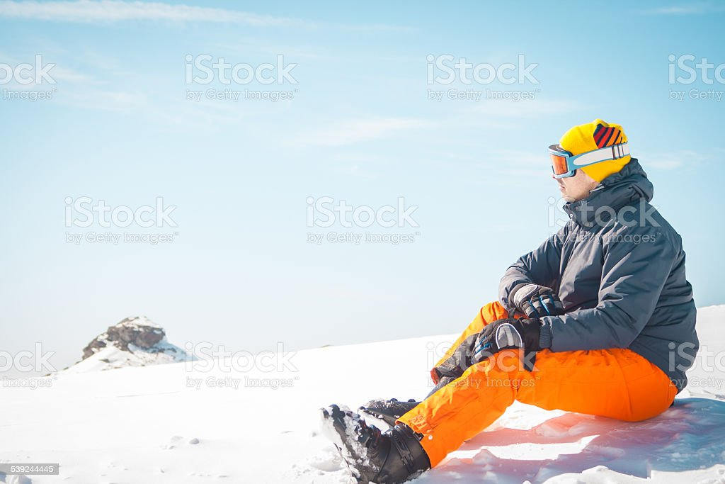Male skier sitting on snow relaxing royalty-free stock photo