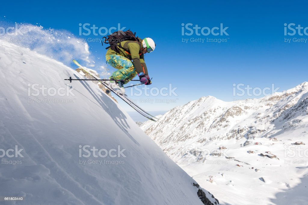 Male skier skiing off piste and jumping in air stock photo