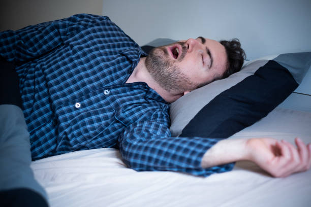 Male snoring loudly in his bed at home stock photo