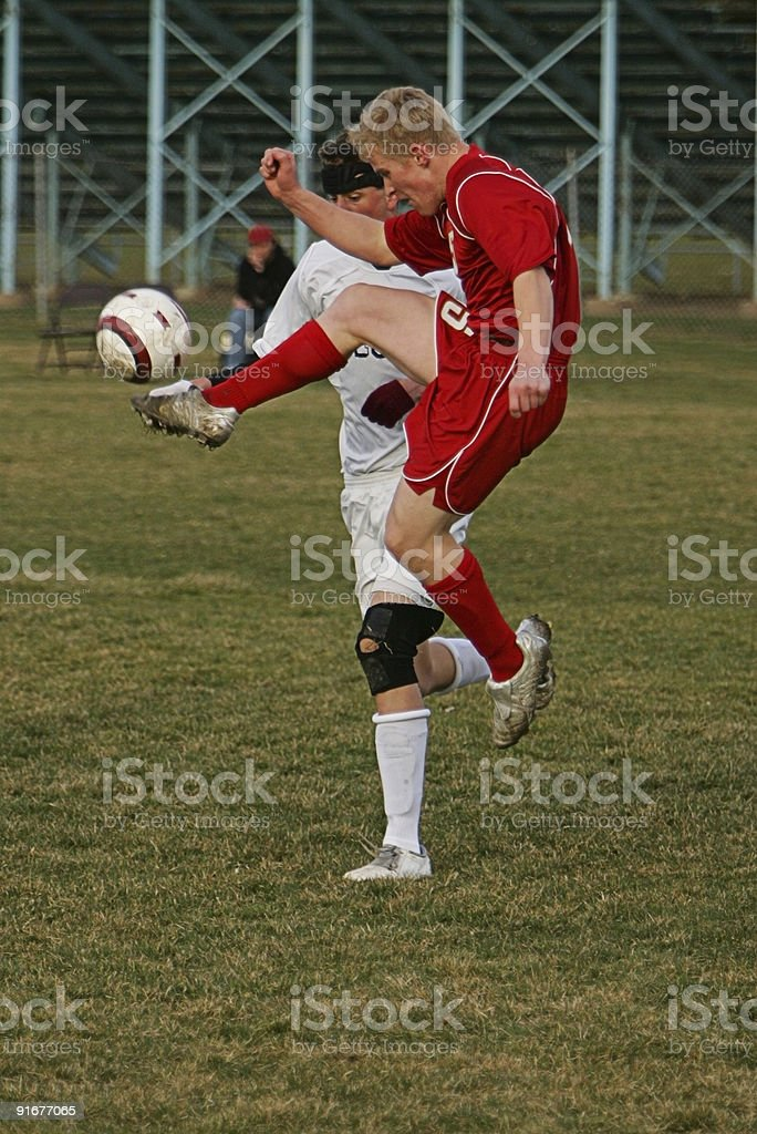 Male Soccer Player in Red Jumps for High Kick royalty-free stock photo