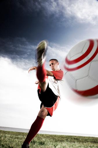 Male soccer player kicking ball at a camera