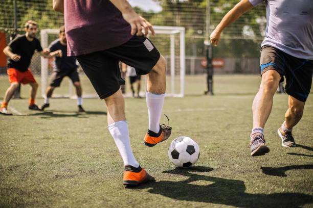 Male soccer player kicking soccer ball stock photo