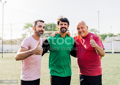 Smiling players showing thumbs up at soccer ground. Male friends with arm around against sky during sunny day. They are in sports uniforms.