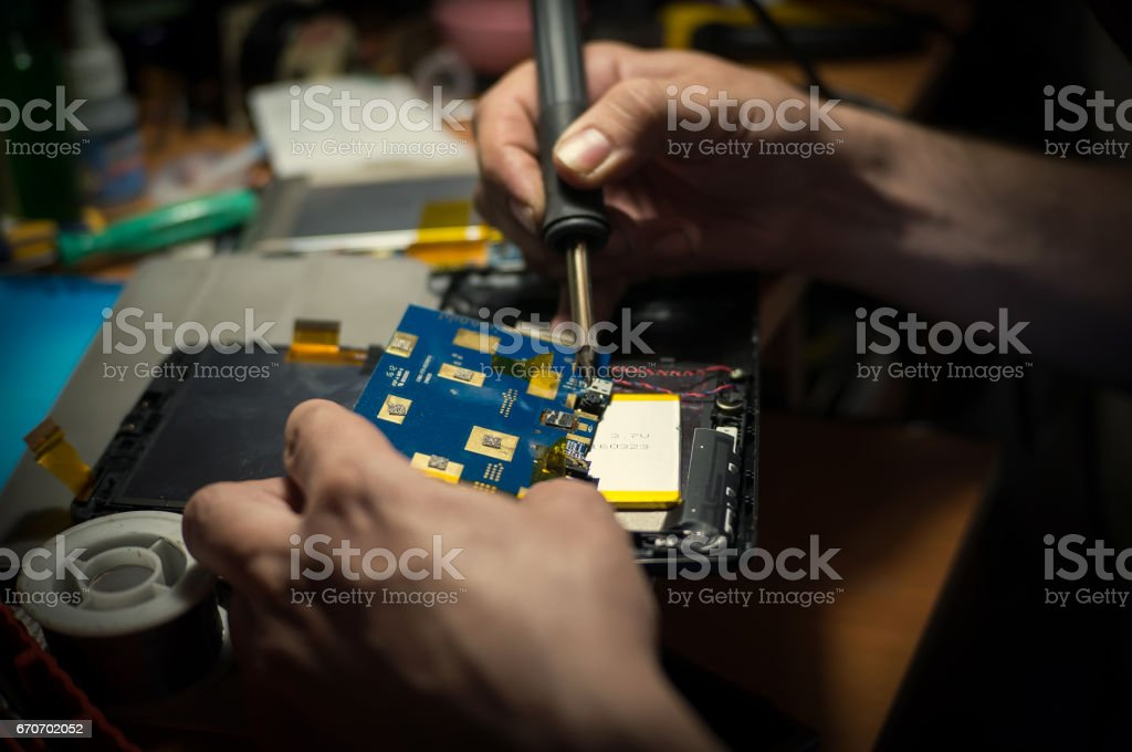 Male solder parts smartphone, repair stock photo
