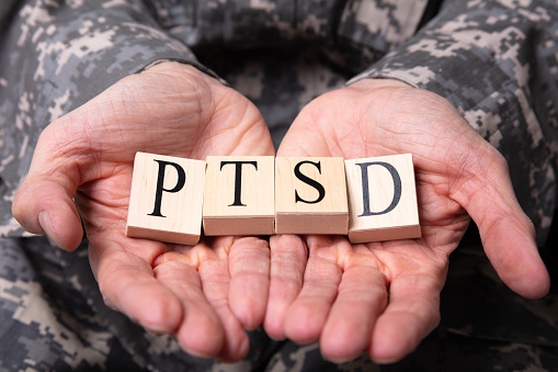 istock Male Soldier Holding Wooden Cubes With PTSD Text 1141354731