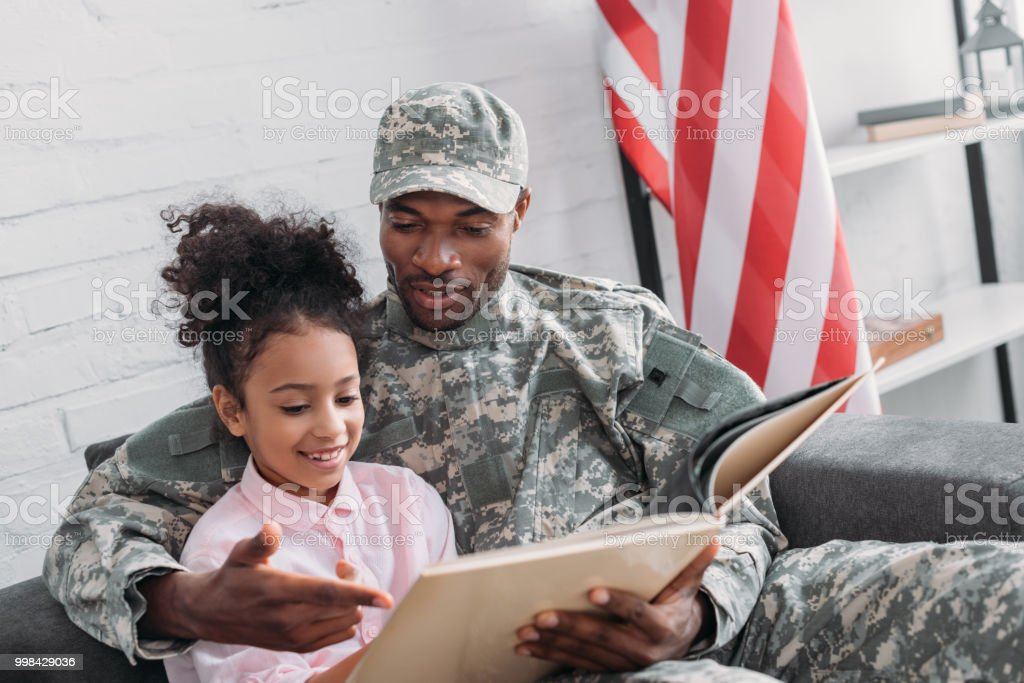 Male soldier reading book to his daughter stock photo