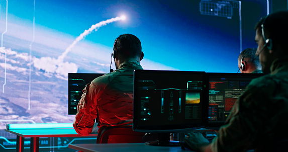 Zoom in view of military men using computers to watch online broadcast and launch nuclear missile during work in control center during world war