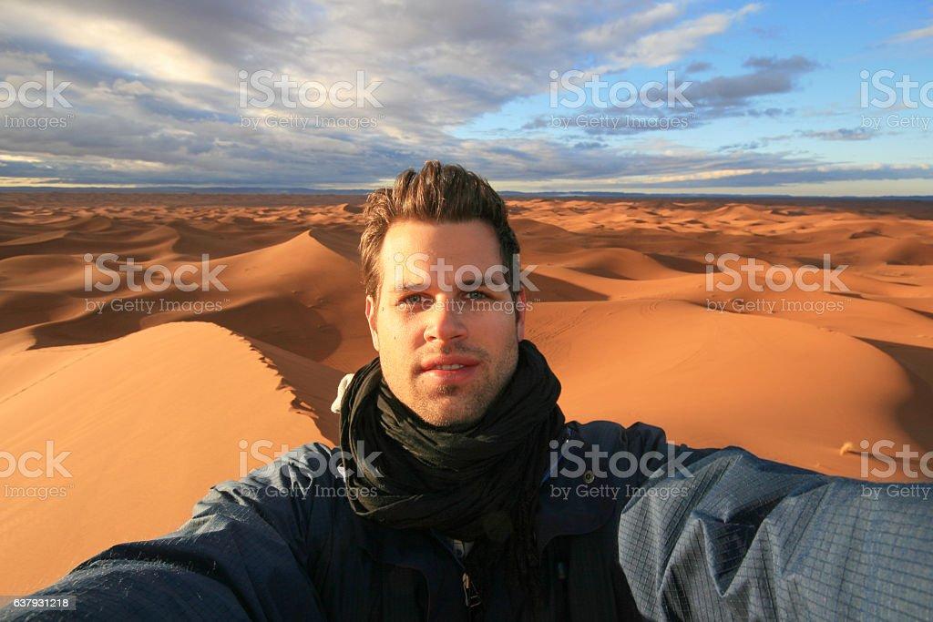Male solo traveler taking selfie in Sahara desert, Morocco. stock photo