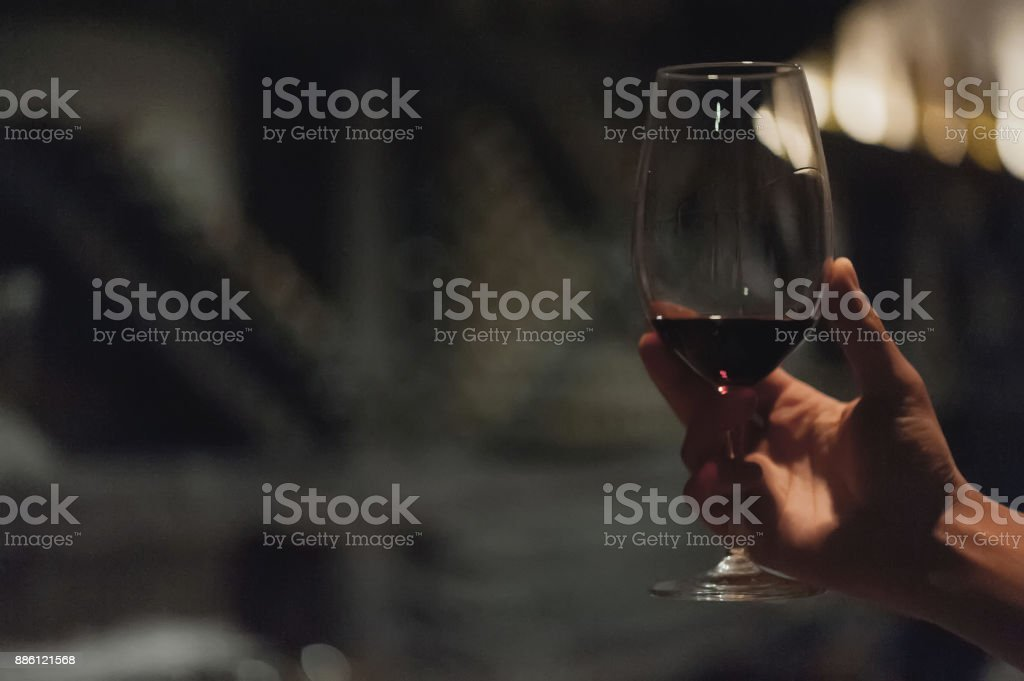 Male sommelier pouring holding wine in long-stemmed wineglasses. stock photo