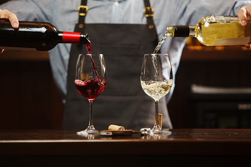 Male sommelier pouring red and white wine into long-stemmed wineglasses