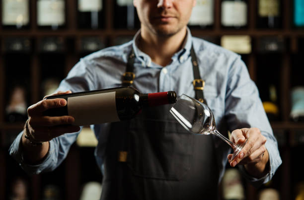 male sommelier pouring red wine into long-stemmed wineglasses. - assaggiare foto e immagini stock