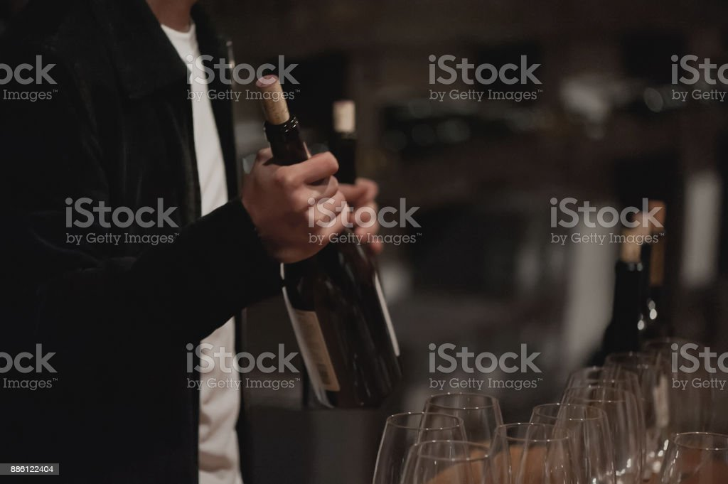 Male sommelier pouring red wine into long-stemmed wineglasses. stock photo