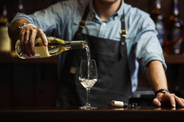Male sommelier pouring white wine into long-stemmed wineglasses. Male sommelier pouring white wine into long-stemmed wineglasses. Waiter with bottle of alcohol beverage. Bartender at bar counter pour elite drink into long-stemmed glass pouring stock pictures, royalty-free photos & images