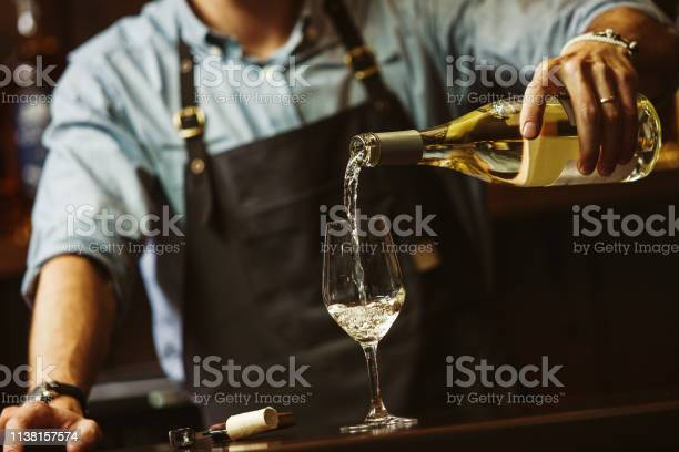 Male sommelier pouring white wine into longstemmed wineglasses picture id1138157574?b=1&k=6&m=1138157574&s=612x612&h=7cbbleq7wqstbzzd62fawpa4sseauael1pmt2rkn9yi=