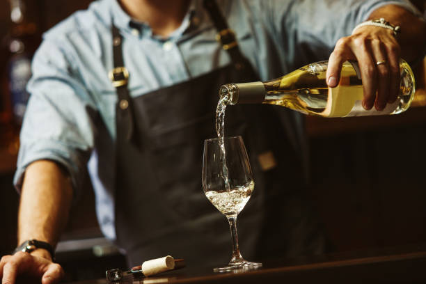Male sommelier pouring white wine into long-stemmed wineglasses. Male sommelier pouring white wine into long-stemmed wineglasses. Waiter with bottle of alcohol beverage. Bartender at bar counter pour elite drink into long-stemmed glass white wine stock pictures, royalty-free photos & images