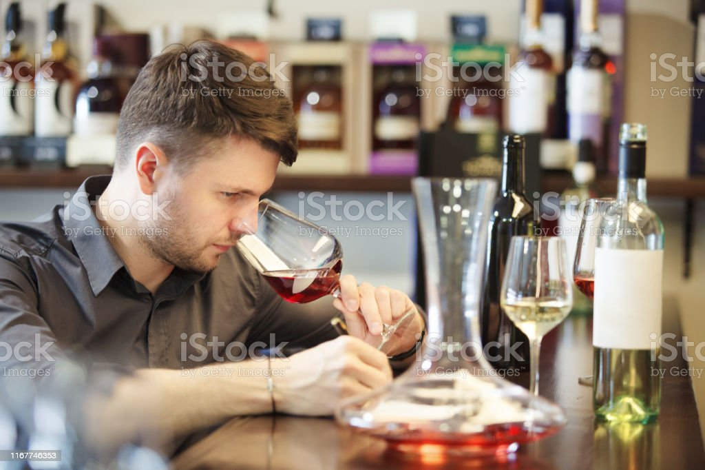 Male sommelier tasting red and white wine, making notes at bar...