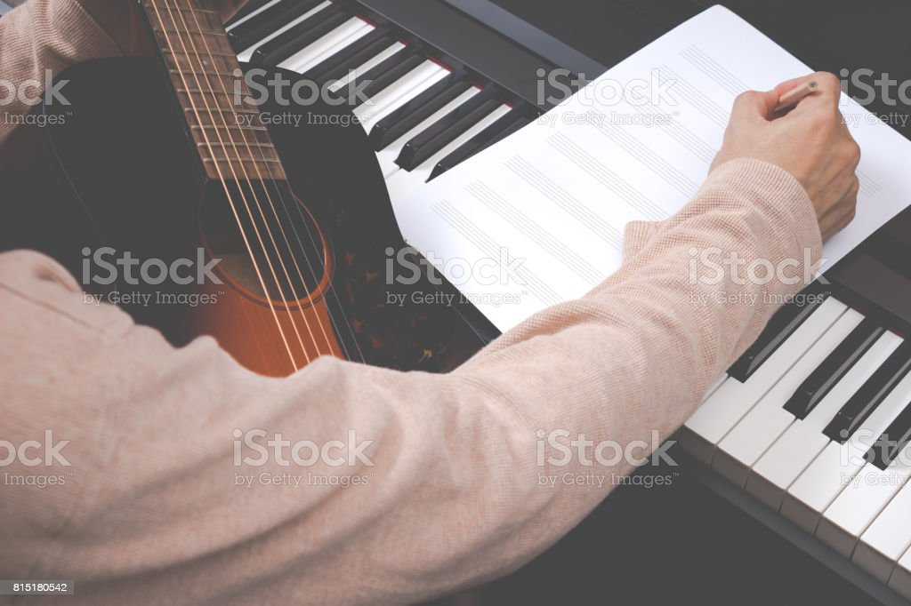 male songwriter writing song on blank music sheet stock photo