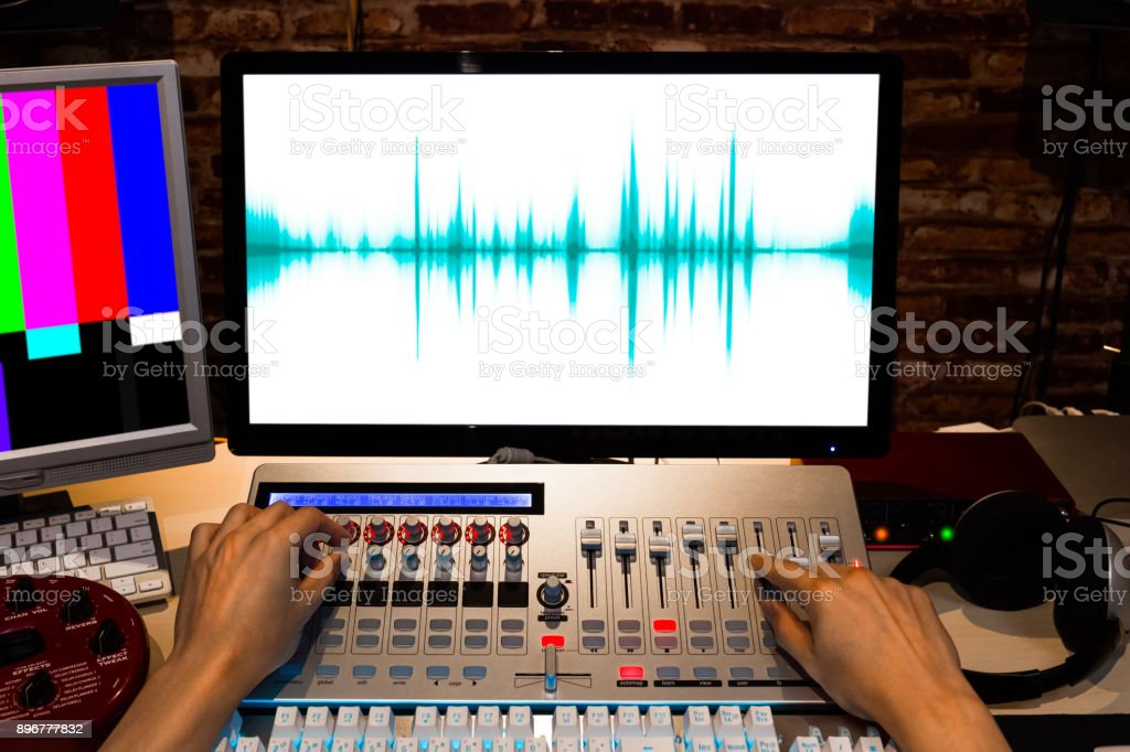 male sound engineer hands control digital sound mixer workstation in tv station editing studio stock photo