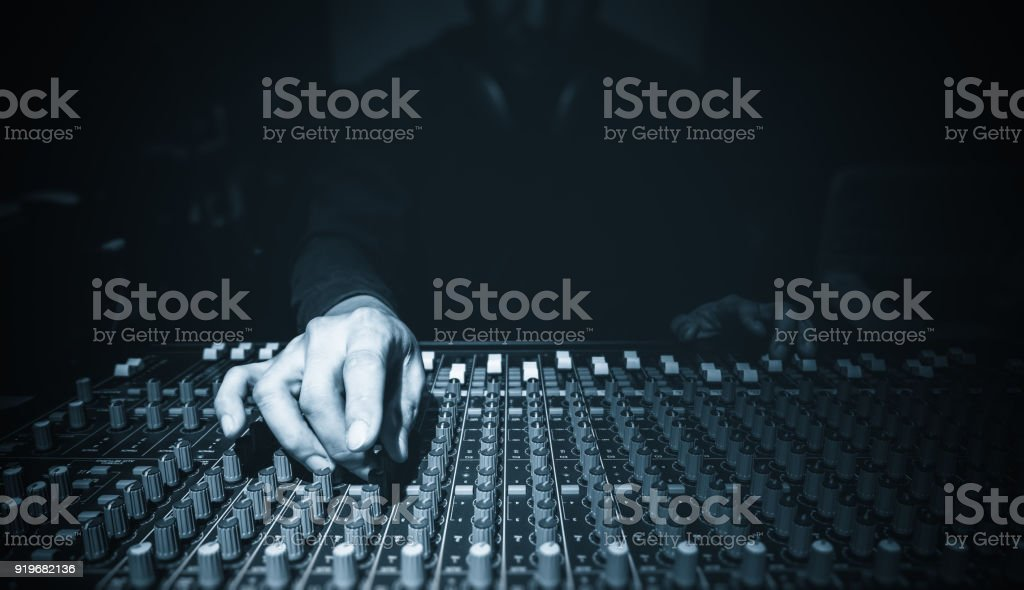 male sound engineer hands working on audio mixing console in recording studio stock photo