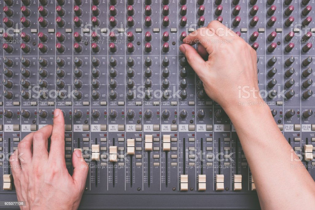 male sound engineer hands working on audio mixing console stock photo