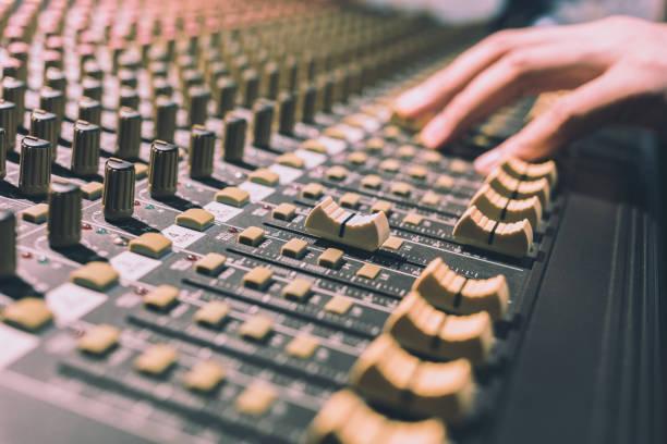 männliche tontechniker hände an sound-mixer arbeiten konzentrieren sich auf fader. aufnahme, rundfunk, musik-produktion-hintergrund - postproduktion stock-fotos und bilder