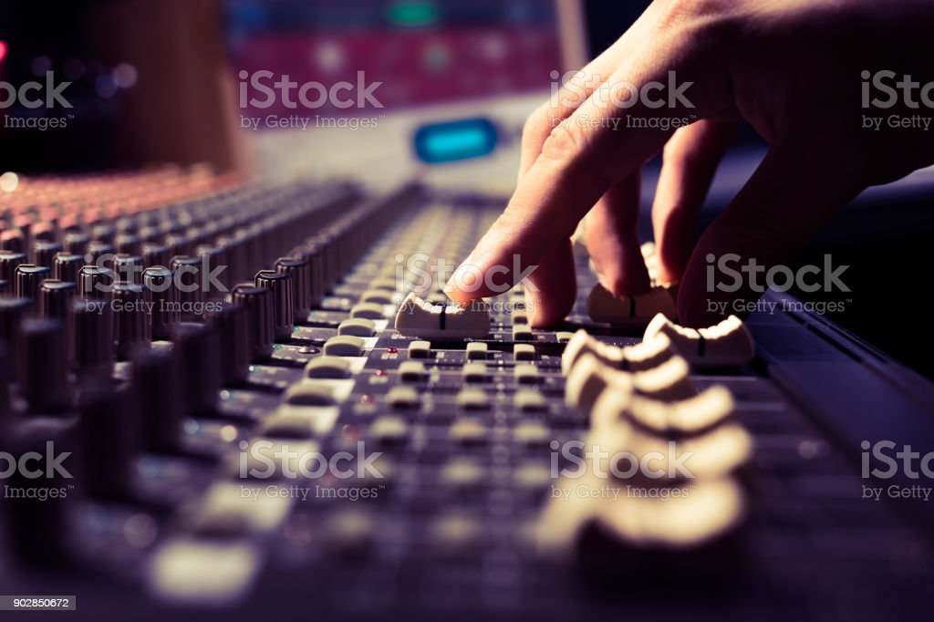 male sound engineer hands working on sound mixer for recording, broadcasting, music production background stock photo