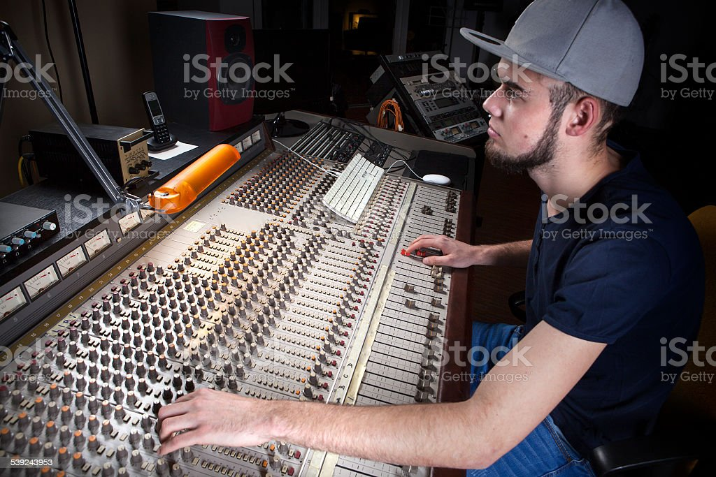 Male sound engineer using a studio mixing desk royalty-free stock photo