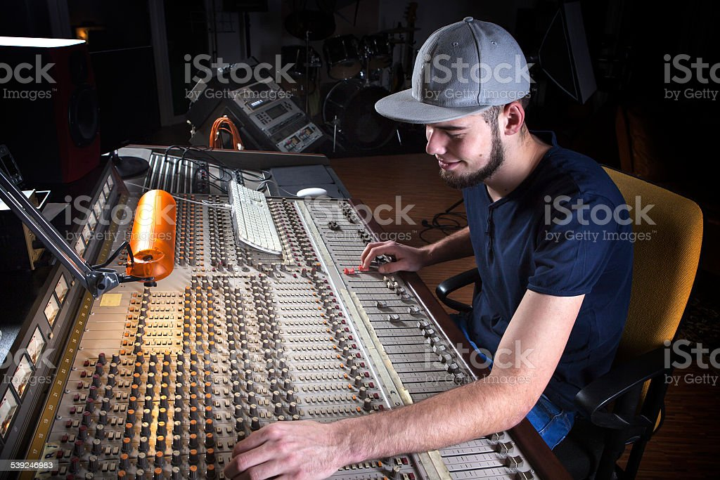 Male sound engineer using a studio mixing desk stock photo