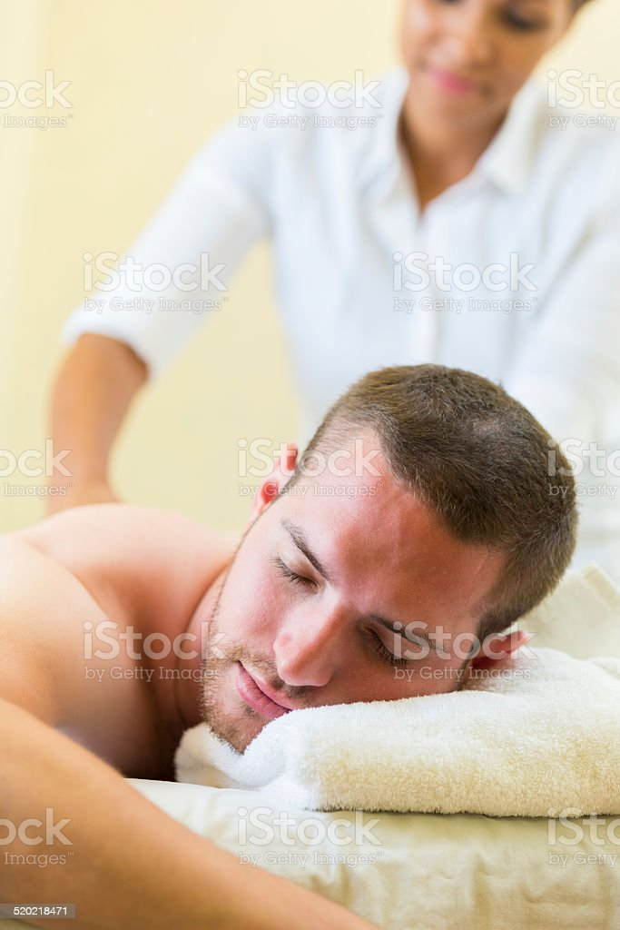 Male spa customer relaxing during massage